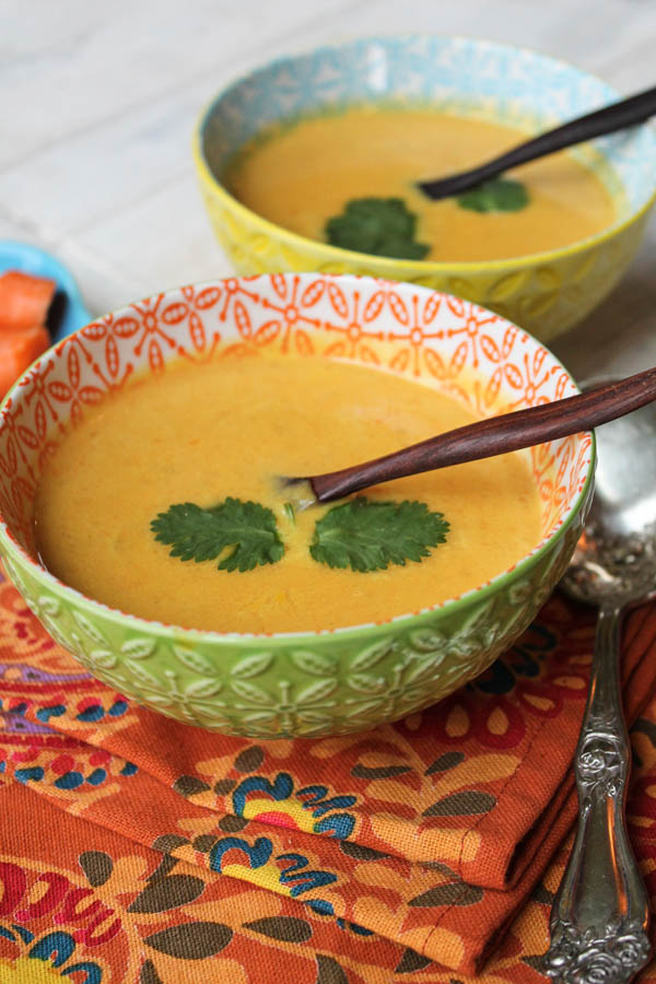 vertical image of two bowls of thai carrot soup with a cilantro garnish on an orange linen