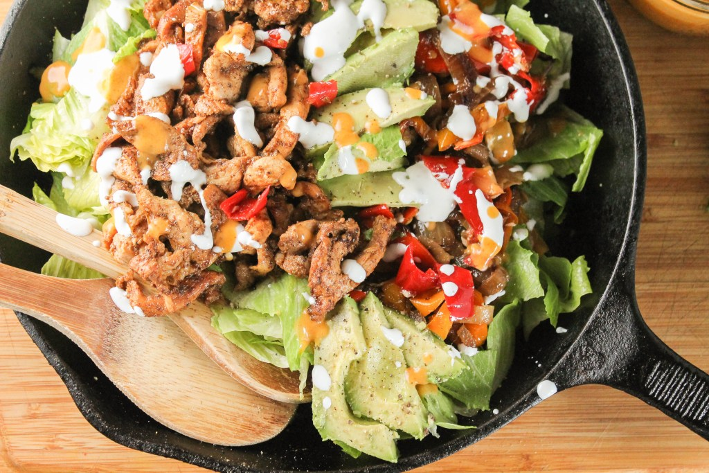 horizontal image of paleo chicken fajitas with charred onions and peppers topped with a dairy free creamy drizzle in a cast iron pan with wooden serving spoons