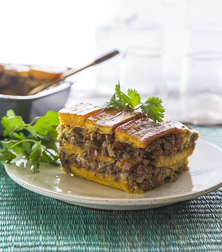 a vertical image of a layered sauteed plantain and ground beef casserole on a white plate