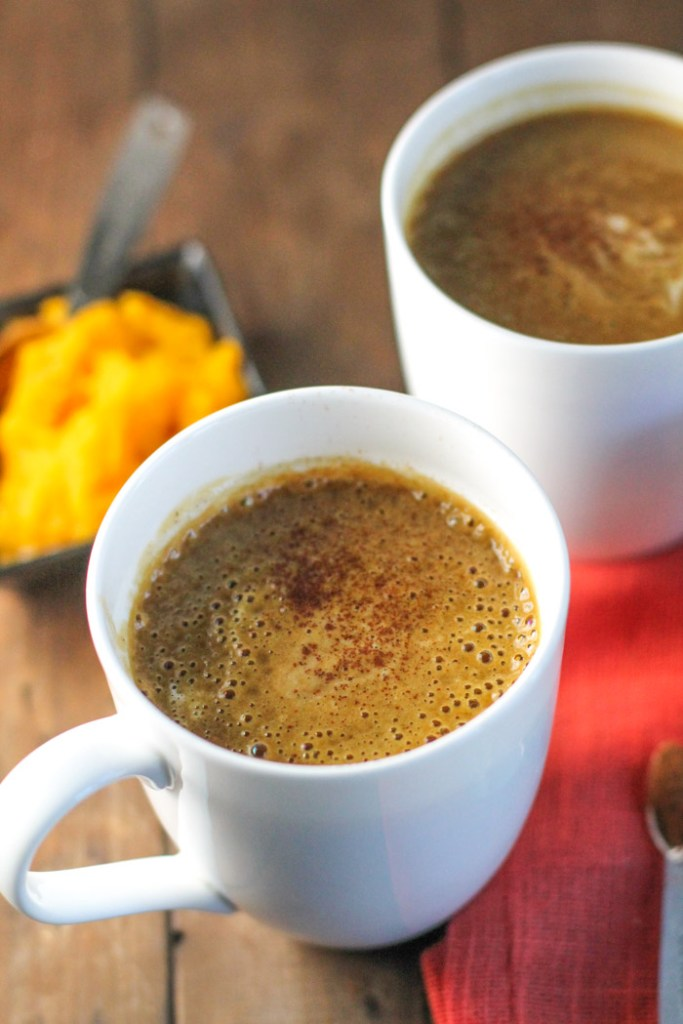 vertical image of two white mugs filled with an orange hued coffee drink with a dish of fresh pumpkin puree and a fall colored linen