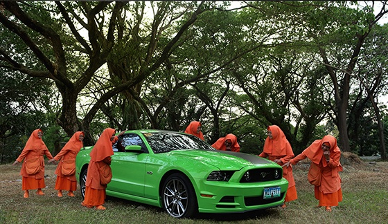 Monks standing around a green Mustang