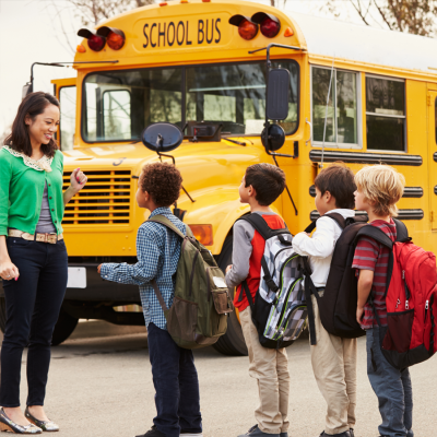 A teacher with four students waiting in a line in front of a school bus.