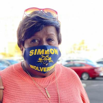 """Photo of Vanessa Betts in a parking lot, wearing a """"Simeon Wolverines"""" face mask."""