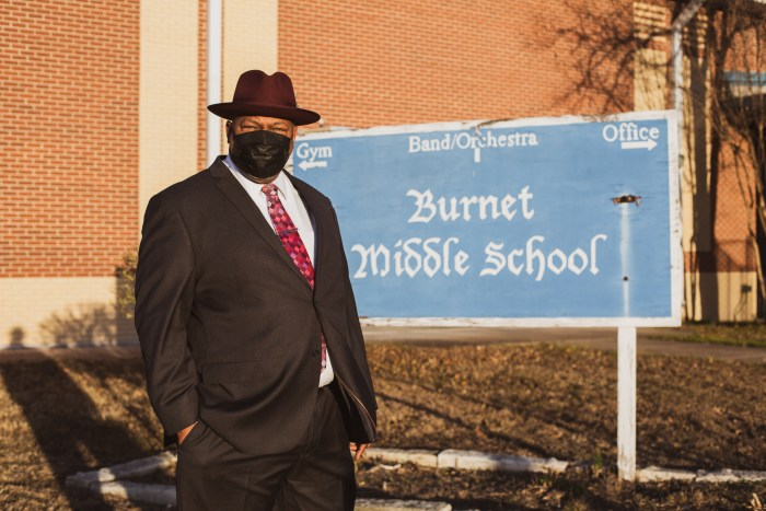 Member wearing a suit and a face mask standing next to a Burnet Middle School sign.