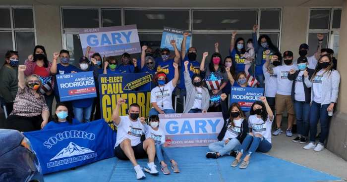 Socorro A-F-T members and allies pose for a photo outside a building. Everyone is wearing face masks and some are holding signs for endorsed school board candidates.