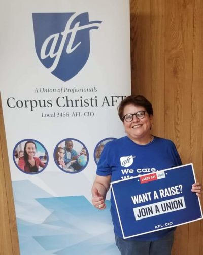 """Doctor Nancy Vera stands in front of a Corpus Christi A-F-T banner. She holds a sign that reads, """"Want a raise? Join a union."""""""