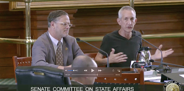 Ken Zarifis testifies in the Legislature. He is sitting next to another person at the table and gesturing emphatically.