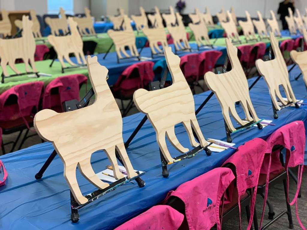 Paint party supplies - plastic table cloth, pink aprons, and rows of wooden llamas ready to be painted