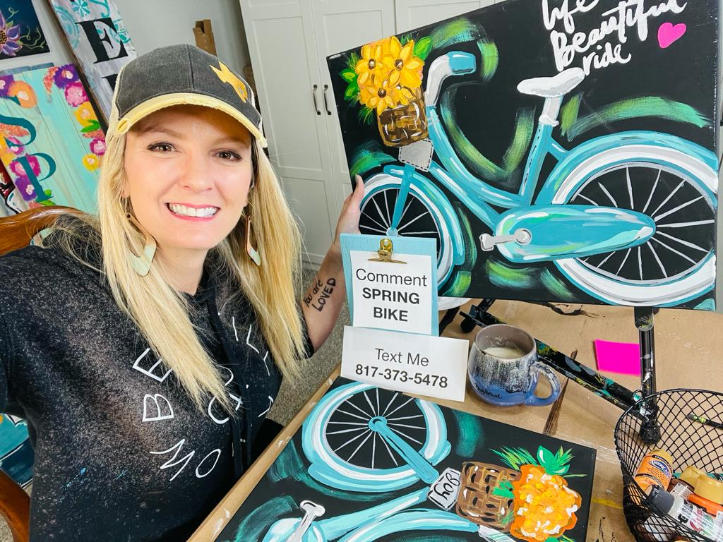 heidi ealsey with acrylic painting of blue bike with flower basket