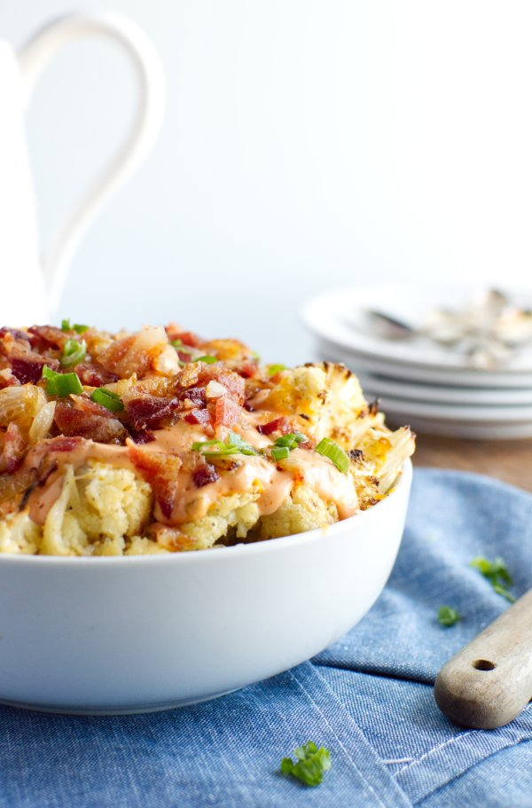 Bowl of roasted cauliflower topped with sauce bacon and green onion