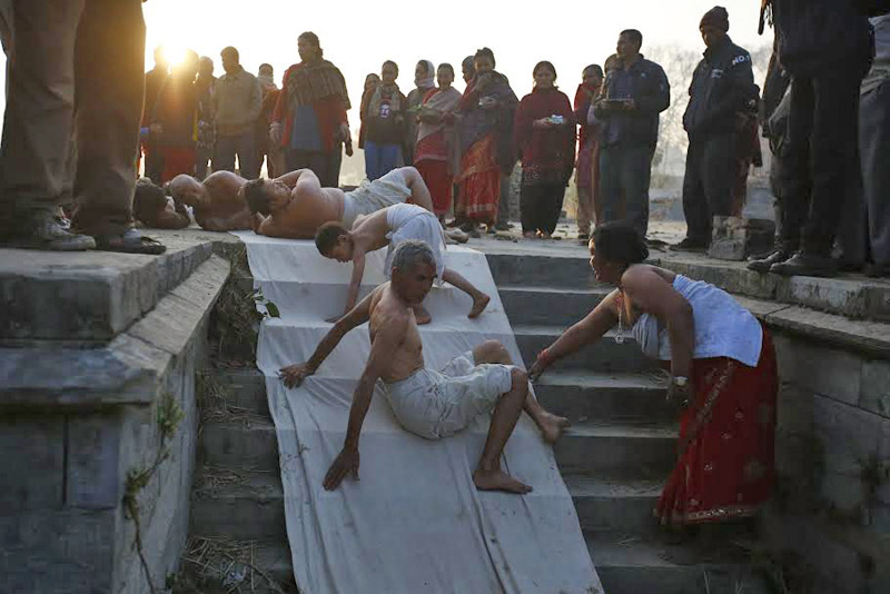 Devotees offer prayers by rolling down on the ground on the last day of month-long Swasthani Brata Katha and Madhav Narayan festival in Kathmandu, on Monday, February 22, 2016. Photo: Skanda Gautam/ The Himalayan Times