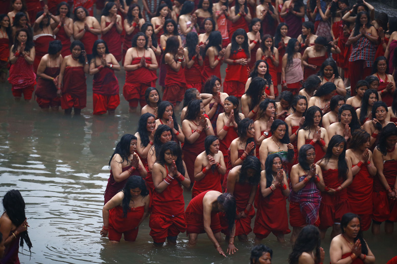 Devotees recite the holy scripture of Swasthani Brata Katha and offer prayer before taking a holy dip in Pashupati area during the month-long Swasthani Brata Katha festival, devoted to goddess Shree Swasthani, in Kathmandu on Monday, February 8, 2016. Photo: Skanda Gautam/The Himalayan Times