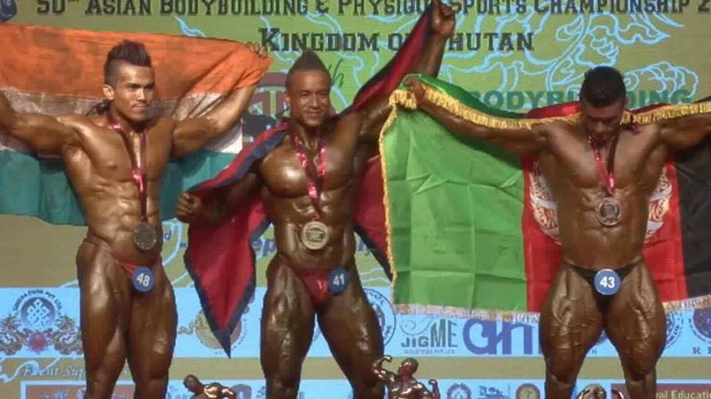 Nepal's Maheshwor Maharjan (centre) celebrates on the podium after winning gold medal in the 50th Asian Body Building Championship in Thimpu on Tuesday, September 6, 2016.