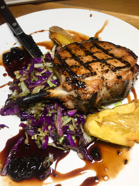 Grilled Pork Chop with Red Wine Reduction, Cherries with Seared Purple Cabbage and Potato.