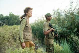 Marie Colvin (Rosamund Pike) enters the Sri Lankan jungle in A PRIVATE WAR.