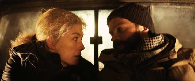 (L to R) Marie Colvin (Rosamund Pike) and Paul Conroy (Jamie Dornan) fearfully drive through a warzone in A PRIVATE WAR.