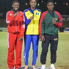 Asha James, left, stands proudly after winning Girls under-18 silver in the javelin throw event. She launched the spear 45.12 metres for her best throw. Photos courtesy THA Info Dept.