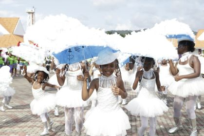 Wearing white frilly dresses and shielded from the hot sun by umbrellas, Zante Dancers displayed 'Elements that brighten the sky'.