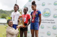 Assistant Secretary in the Office of the Chief Secretary Marisha Osmond presents the winner's trophy to Jelesia Alexander, of Scarborough RC, while second placed Olivia Ramsaran of Signal Hill Government, second from left, and Jelisha Pollard, right, third, of Pentecostal Light and Life Ministries Primary School.