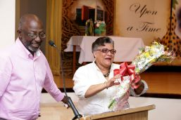 Tobago Institute of Literacy executive officer Susan Sandiford reacts on receiving a bouquet of flowers in appreciation for her service to the organisation from outgoing chairman of the board of directors John Solomon.