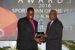 Akeem Stewart receives his trophy for THA Sportsman of the Year 2016 from Chief Secretary Kelvin Charles.
