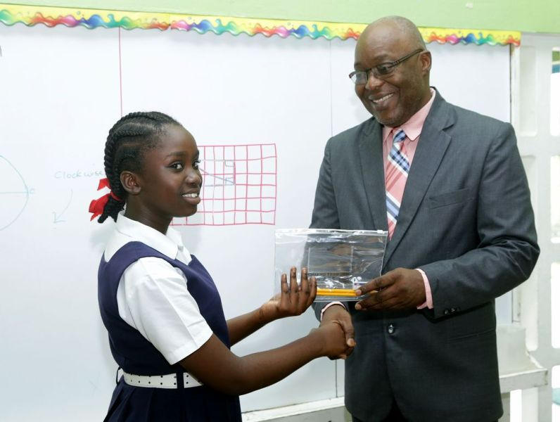 Whim Anglican pupil Kavi Taylor gets her stationery package from Chief Secretary Kelvin Charles.