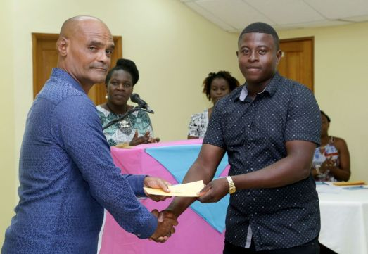 """Buccoo Village Council public relations officer Winston Pereira, left, presents Gerome Clarke with the winner's prize for the C2 Class race won by the goat """"Easy Target."""""""