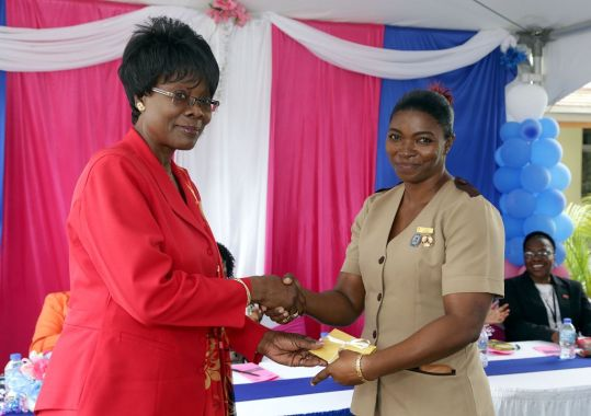 Secretary of Health, Wellness and Family Development Dr Agatha Carrington presents Carla Newsam-Blake with a gift from her peers. Newsam-Blake was recently promoted from midwife to District Health Visitor.
