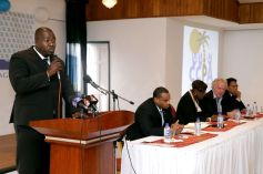 Assemblyman Clarence Jacobs, area representative and Secretary of Settlement, Urban Renewal and Public Utilities, addresses the symposium. Seated at the head table from left are DIQE Secretary Kwesi Des Vignes, Administrator at the DIQE Joan Hannibal-Phillips, president of the Hotel and Tourism Association (THTA) Chris James and CCPA president Garvin Monzano.