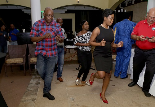 Chief Secretary Kelvin Charles and Secretary of Tourism, Culture and Transportation Councillor Nadine Stewart-Phillips do the electric boogie with guests at the reception.