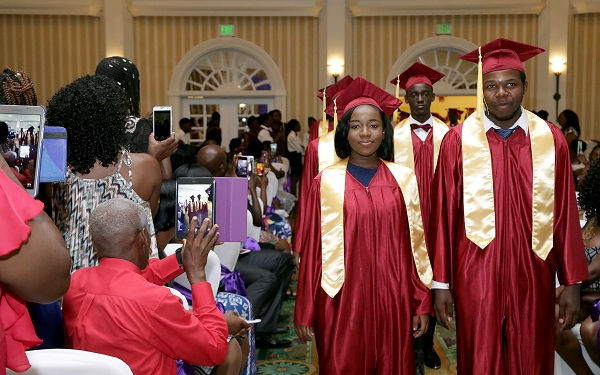 Relatives and friends record the moment as graduates enter the ballroom for the start of their graduation ceremony.