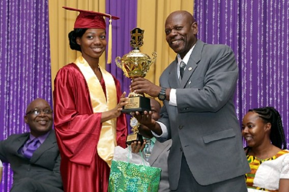 Harmon School of Seventh Day Adventists board chairman Pastor Martin Cunningham presents Carlesia McEwen with an award for the student who has had the most spiritual influence on her peers.