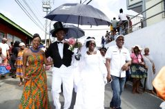"""The """"bride"""" and """"groom"""" lead the procession through Moriah, accompanied by Chief Secretary Kelvin Charles, right, and Tourism, Culture and Transportation Secretary Nadine Stewart-Phillips, left."""