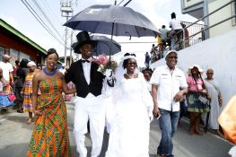 "The ""bride"" and ""groom"" lead the procession through Moriah, accompanied by Chief Secretary Kelvin Charles, right, and Tourism, Culture and Transportation Secretary Nadine Stewart-Phillips, left."