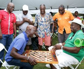 Prime Minister Dr. Keith Rowley plays a game of checkers with Mason Hall villager Courtland Dennis. Also in photo, standing at left, is Chief Secretary Kelvin Charles.