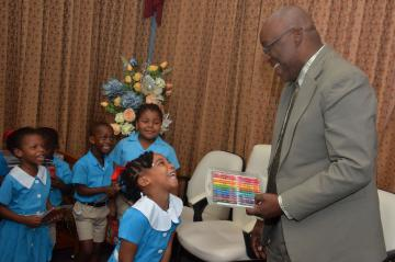 Young Kaelle Walcott, left, is all smiles as receives a gift from Chief Secretary Kelvin Charles.