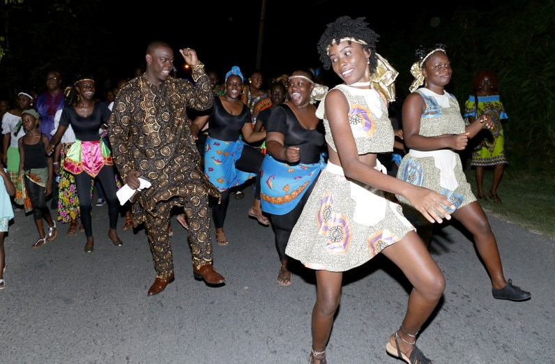 Assistant Secretary of the Division of Community Development, Enterprise Development and Labour Shomari Hector steps in time with members of a dance group who were part of the procession.