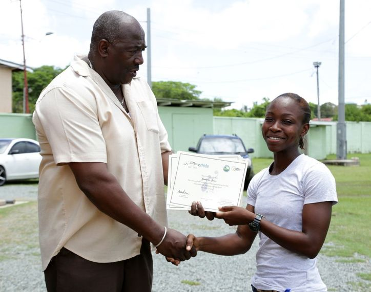 Director of Sport Theophilus Trimm presents Renasha Jones with a certificate of completion for taking part in the Para Sports Level 1 course as a coach/trainer.