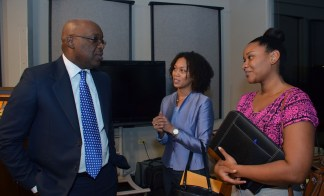 THA Chief Secretary Kelvin Charles, left, talks with WASA representatives, Assistant to the Chairman Raquel Brown, right, and Executive Secretary to the CEO Meiling Wong.