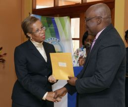 Dr Levis Guy-Obiakor receives her instrument of appointment from THA Chief Secretary Kelvin Charles.