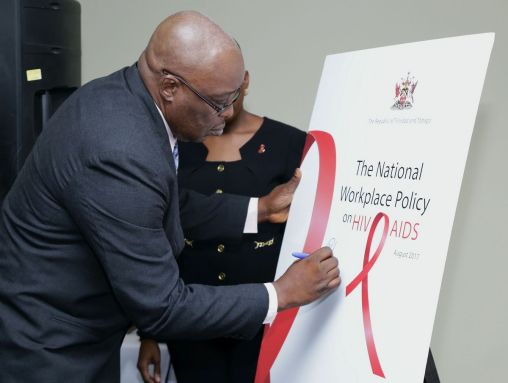 THA Chief Secretary Kelvin Charles endorses the sign board affirming the THA's commitment to the National Workplace Policy on HIV and AIDS.