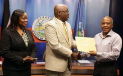 Chief Secretary Kelvin Charles presents Ronald Celestine with his instrument of appointment as chairman of the State Lands Board during the ceremony. At left is acting Chief Administrator Claire Davidson-Williams.