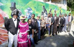 Proud representatives stand in front of the mural after the ceremony. The mural was created by artist Di-Shon Abel.