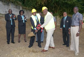 Chief Secretary Kelvin Charles, third from right, turns the sod with Fire Service Credit Union president Marlon Charles to mark the start of construction of the new Fire Service Credit Union building at Rockley Vale last Thursday afternoon. Behind them are members of the credit union board.