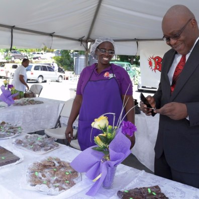 Lois McCollin, left, is all smiles as Chief Secretary Kelvin Charles visits the tent of Bago's homestyle caterers.