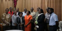 The recipients join Chief Secretary Kelvin Charles, third from right, back row, for a group shot.