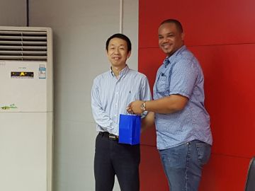 Infrastructure Secretary Kwesi Des Vignes presents a token to Han Wenhua, Director of China Railway Construction Company, Caribbean Ltd.