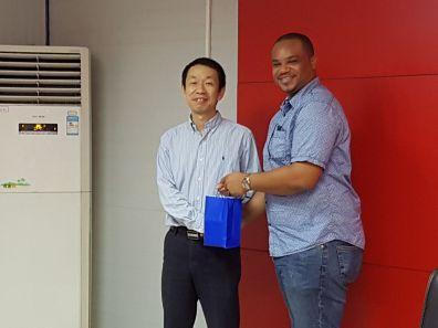 Infrastructure Secretary Kwesi Des Vignes presents a token to Han Wenhua, Director of China Railway Construction Company, Caribbean Ltd.