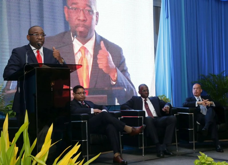 Moderator Economist Hayden Blades directs a panel discussion at the conference. Panelists seated from left are Unit Trust Corporation Executive Director Ian Chinapoo, Economist Terrence Farrell and Antigua and Barbuda's Ambassador Extraordinary and Plenipotentiary to the US and Organisation of American States Sir Ronald Sanders.