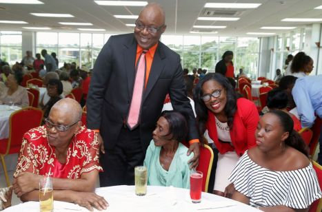 Chief Secretary Kelvin Charles welcomes guests seated at a table.